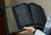 Photo of ہاتھ کی کڑاہی سے سلک کے کپڑے پر سونے سے قرآن مجید تحریر